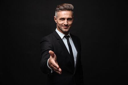 Confident attractive businessman wearing suit standing isolated over black background, outstretched hand fir greeting