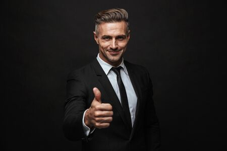 Handsome confident businessman wearing suit standing isolated over black background, thumbs up Banco de Imagens
