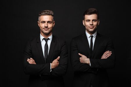 Two confident handsome businessmen wearing suit standing isolated over black background, arms folded