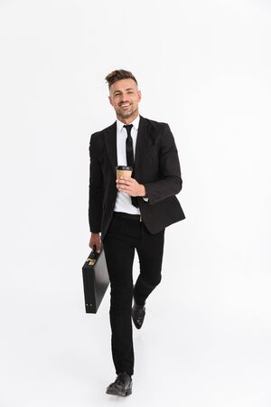 Full length portrait of a handsome confident businessman wearing suit walking isolated over gray backgorund, carrying briefcase, drinking coffee Archivio Fotografico