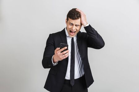 Image of scared caucasian businessman in formal suit holding cellphone and screaming with his hand on his had isolated over gray background