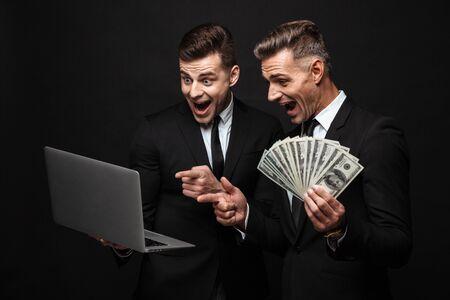Retrato de emocionados dos hombres de negocios caucásicos vestidos con traje formal sosteniendo portátil y billetes de dinero aislados sobre pared negra
