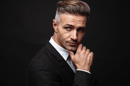 Retrato de hombre de negocios europeo sin afeitar vestido con traje formal posando a la cámara y mirando a un lado aislado sobre pared negra