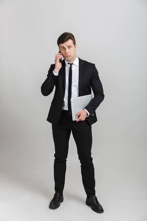 Full length image of perplexed businessman in formal suit frowning while holding cellphone and laptop isolated over gray background
