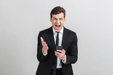 Image of angry yong businessman in formal suit typing on cellphone and screaming at camera isolated over gray background