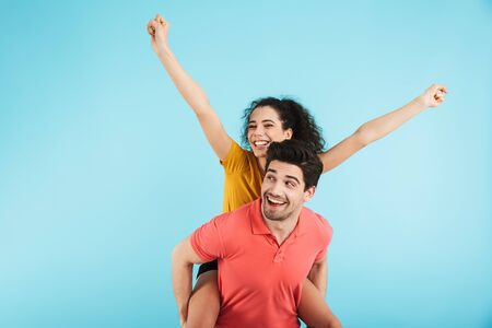 Cheerful young couple standing isolated over blue background, piggyback ride