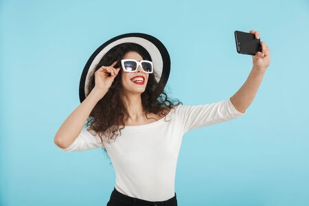 Happy beautiful brunette woman wearing summer outfit with hat and sunglasses standing isolated over blue background, taking a selfie Stock Photo