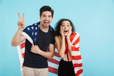 Cheerful young couple standing isolated over blue background, wearing american flag Imagens