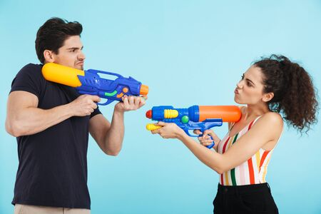 Cheerful young couple standing isolated over blue background, having fun with water guns Stock Photo