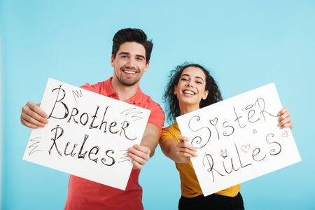 Happy cheerful brother and sister standing isolated over blue background, showing banners with lettering