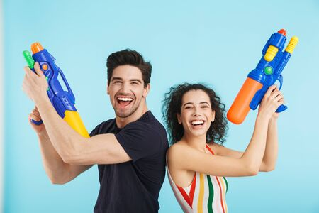 Cheerful young couple standing isolated over blue background, having fun with water guns Banque d'images