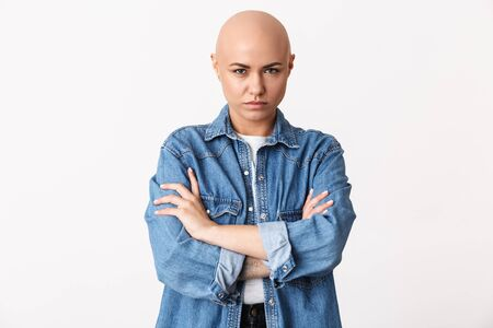 Portrait of an upset beautiful young hairless woman wearing casual clothes standing isolated over white background 免版税图像