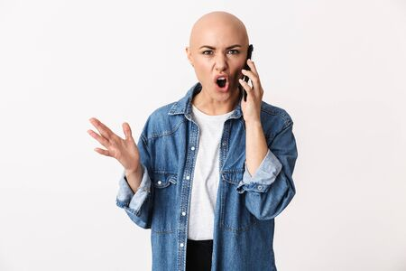 Image of a beautiful displeased angry bald woman posing isolated over white wall background talking by mobile phone.