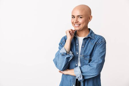 Image of a beautiful happy bald woman posing isolated over white wall background.