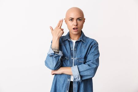 Image of a beautiful displeased bald woman posing isolated over white wall background make gun gesture.