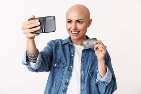 Image of a beautiful happy bald woman posing isolated over white wall background talking by mobile phone take a selfie holding credit card.