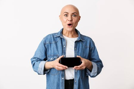 Image of a shocked bald woman posing isolated over white wall background showing display of mobile phone.