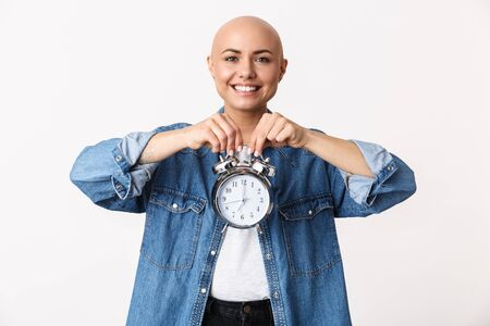 Portrait of a beautiful young hairless woman wearing casual clothes standing isolated over white background, showing alarm clock