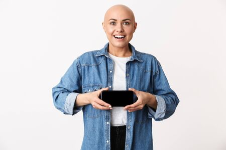 Image of a bald woman posing isolated over white wall background showing display of mobile phone. Stock Photo