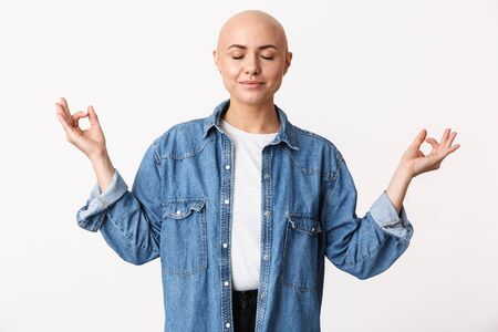 Image of a beautiful amazing pretty bald woman posing isolated over white wall background meditate. Stock Photo