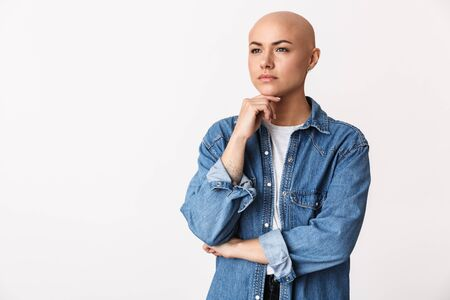 Image of a beautiful thinking bald woman posing isolated over white wall background. Фото со стока