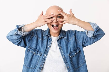 Image of a beautiful happy bald woman posing isolated over white wall background covering face with hands.