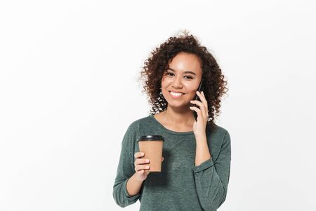 Portrait of a pretty cheerful casual african girl standing isolated over white background, talking on mobile phone, drinking takeaway coffee Stock Photo