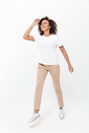 Full length of a happy young african woman wearing casual clothes isolated over white background, looking far away