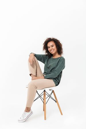 Attractive young african woman sitting on a chair isolated over white background, posing Banque d'images
