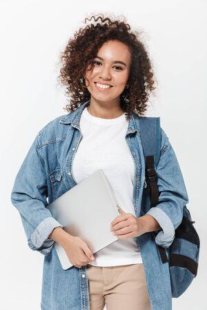 Retrato de una niña africana casual bastante alegre que lleva la mochila que se encuentran aisladas sobre fondo blanco, sosteniendo la computadora portátil Foto de archivo