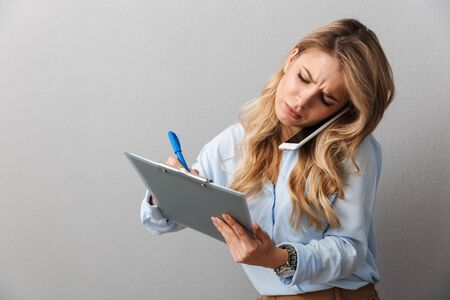 Photo of serious blond secretary woman with long curly hair writing down notes in clipboard while calling on smartphone isolated over gray background