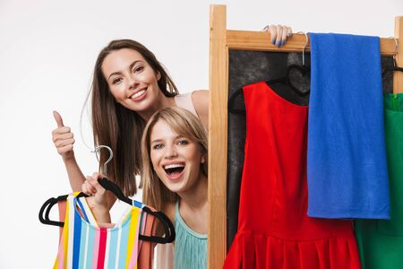 Two cheerful pretty young girls isolated over white background, shopping together, holding cloth racks with dresses
