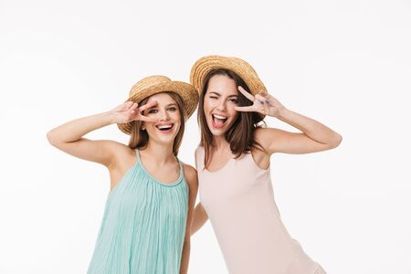 Two cheerful young girls wearing summer clothes standing isolated over white background, showing peace gesture Stock Photo