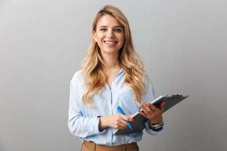 Photo of gorgeous blond secretary woman with long curly hair writing down notes in clipboard while working in office isolated over gray background Stock Photo