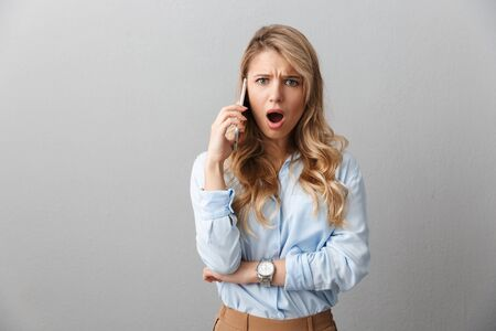 Photo of concerned blond businesswoman with long curly hair worrying while calling on smartphone isolated over gray background Stock Photo