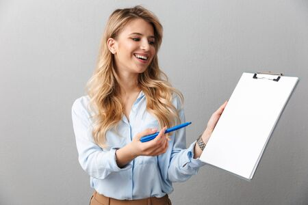 Photo of lovely blond secretary woman with long curly hair writing down notes in clipboard while working in office isolated over gray background Stock Photo