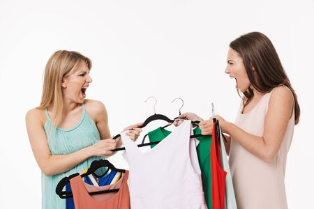 Two angry pretty young girls isolated over white background, shopping together, holding cloth racks with dresses, fighting Stock Photo