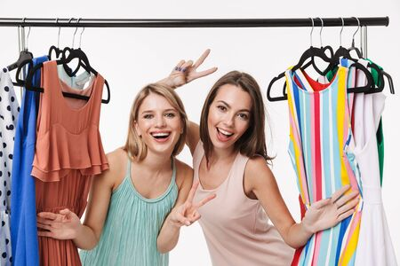 Two cheerful pretty young girls isolated over white background, choosing dresses on a clothes rack