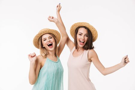 Two cheerful young girls wearing summer clothes standing isolated over white background, celebrating Stock Photo