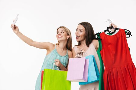 Two cheerful pretty young girls isolated over white background, shopping together, holding cloth racks with dresses, taking a selfie
