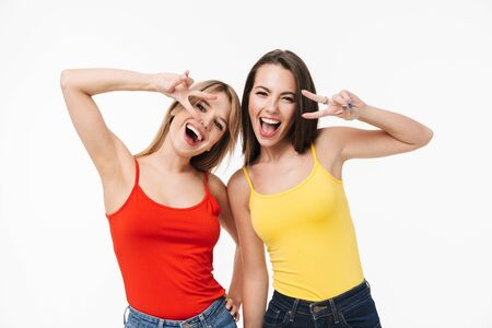 Two cheerful pretty young girls isolated over white background, showing peace gesture
