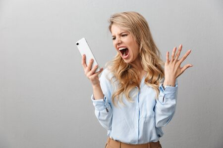 Photo of angry puzzled businesswoman with long curly hair worrying and screaming while calling on smartphone isolated over gray background Zdjęcie Seryjne