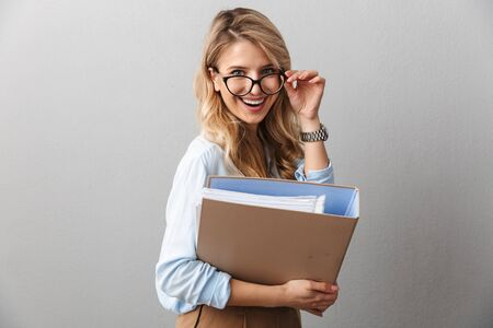 Photo of adorable blond secretary woman wearing eyeglasses smiling and holding file folder while working in office isolated over gray background