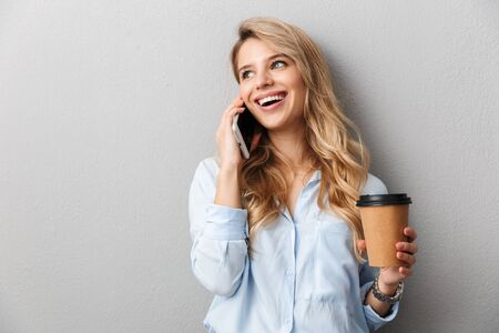 Attractive young blonde businesswoman wearing shirt standing isolated over gray background, holding takeaway coffee cup, talking on mobile phone Stock Photo