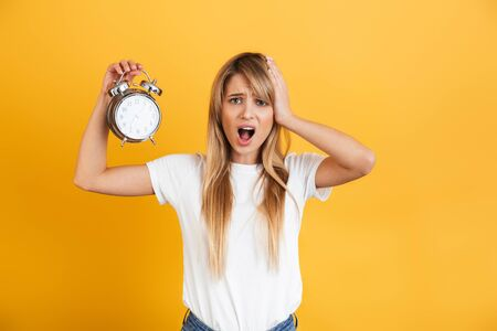 Image of a screaming displeased young blonde woman posing isolated over yellow wall background dressed in white casual t-shirt holding alarm clock.