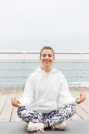 Image of smiling beautiful woman 20s in white hoodie meditating with zen fingers in yoga pose on fitness mat while working out near seaside Stock Photo