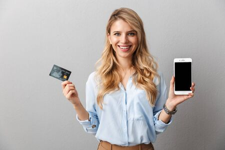 Image of a happy young pretty blonde business woman posing isolated grey wall background holding credit card showing display of mobile phone. Stock fotó