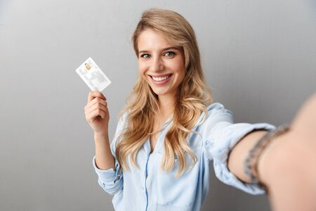 Photo of lovely blond businesswoman smiling and holding credit card while taking selfie isolated over gray background