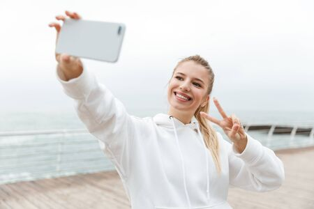 Image of cheerful nice woman 20s in white hoodie taking selfie on cellphone and showing peace sign while walking near seaside