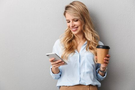Attractive young blonde businesswoman wearing shirt standing isolated over gray background, holding takeaway coffee cup, using mobile phone